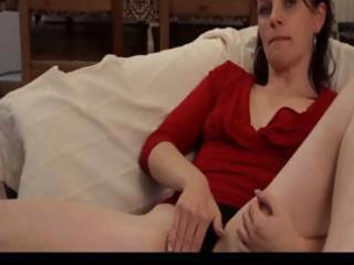 slim dark brown mature is on the couch toying her